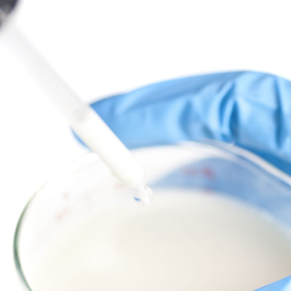close-up of a can of milkclose-up of human hand with gloves testing milk